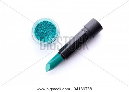 Top view of a lipstick and eye shadow in jar in bright teal green color, isolated on white background