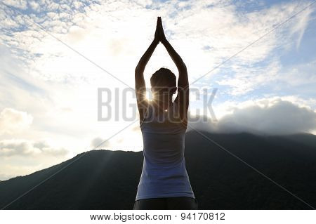 silhouette of young yoga woman at sunrise peak