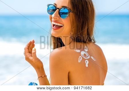 Woman using sun cream on the beach