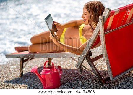 Woman using digital tablet on the sunbed