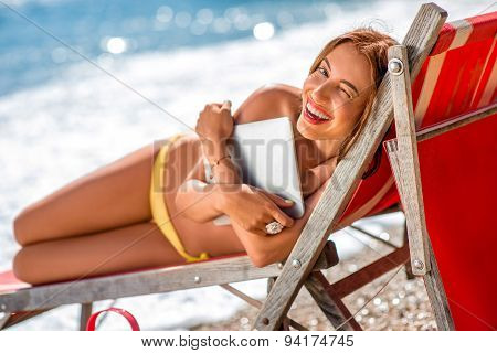 Woman with digital tablet on the sunbed