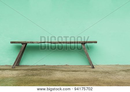 Old Wooden Bench And Green Wall