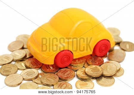 Toy Auto Stand On Pile Of Coins (isolated)