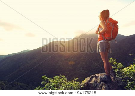 young woman hiker enjoy the beautiful landscape at mountain peak rock