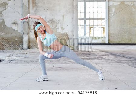 Beautiful Fitness Girl Exercising In Abandoned Building