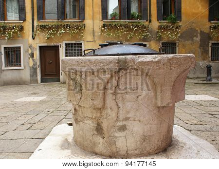 an old stone well with metal lid in the Italian mountains