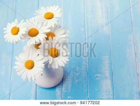 Daisies In A Vase On Blue Wooden Background