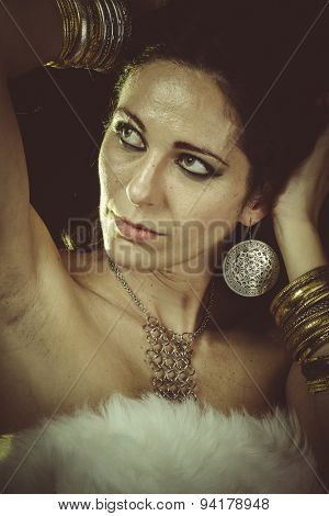 Luxury, brunette woman wearing white fur and gold jewelry