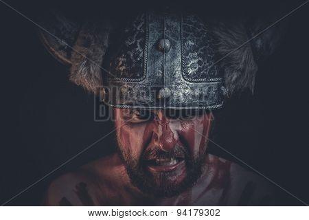 Angry Viking warrior with a horned helmet and war paint on his face