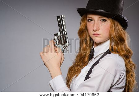 Pretty girl wearing retro hat and holding weapon isolated on gray