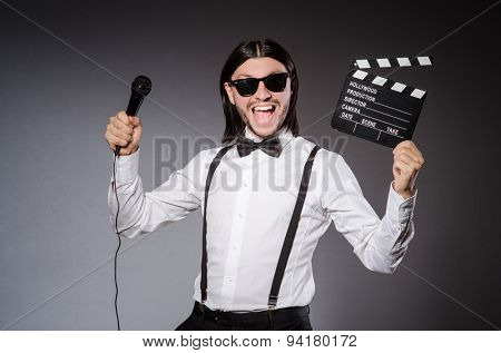 Positive man holding clapperboard and microphone isolated on gray