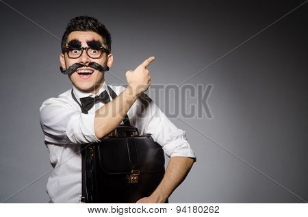 Young man with false moustache holding case isolated on gray