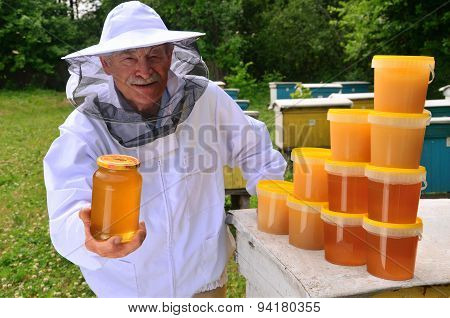 Senior apiarist presenting jar of fresh honey in apiary in the springtime