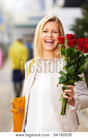 Laughing Woman Posing On Sidewalk Holding Red Roses