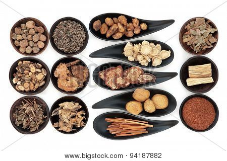 Chinese herbal medicine selection in black bowls  over white background.