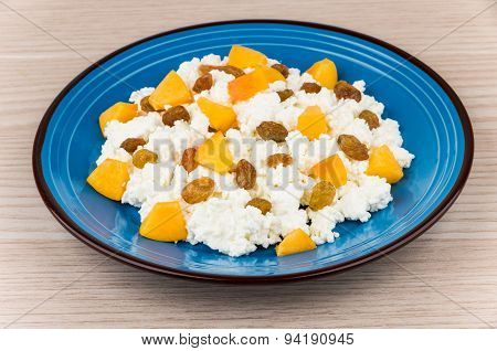 Curd In Glass Plate With Peaches And Raisins On Table