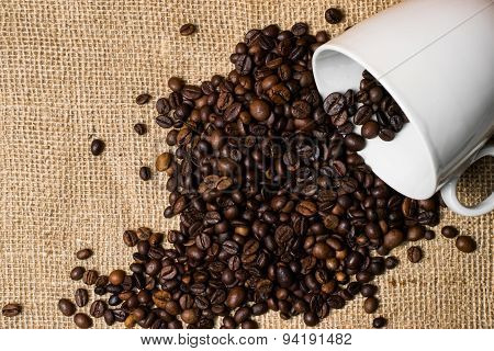 Cup Full Of Coffee Beans Spilled Over Cloth Background