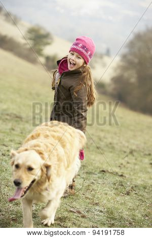 Girl on country walk with dog in winter