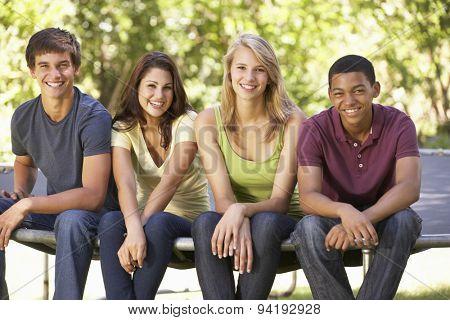 Four Teenage Friends Sitting On Trampoline In Garden