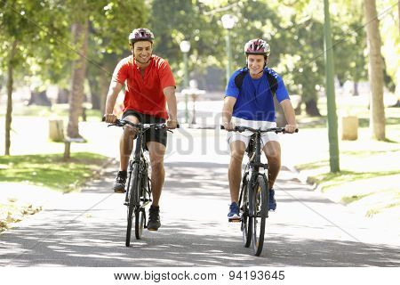 Two Men Cycling Through Park