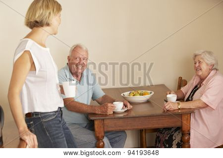 Adult Daughter Sharing Cup Of Tea With Senior Parents In Kitchen