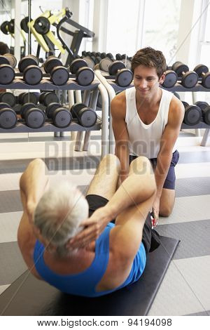 Middle Aged Man Working With Personal Trainer In Gym