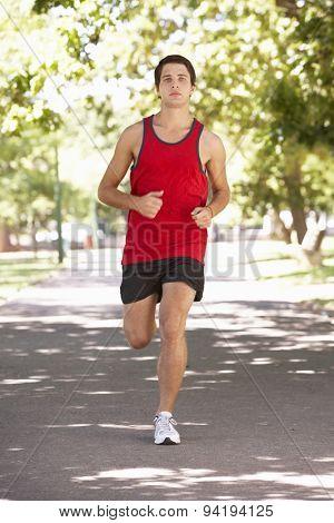 Young Man Running Through Park