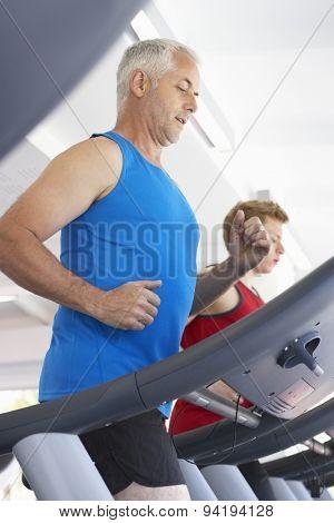 Two Men Using Running Machines In Gym