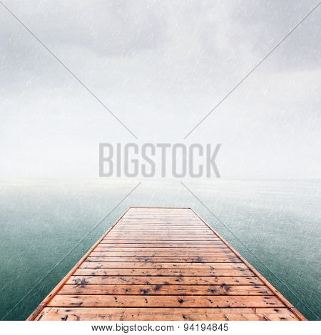 Wooden jetty, pier on deep cold sea, ocean. Raining sky, scandinavian mood, copy-space.