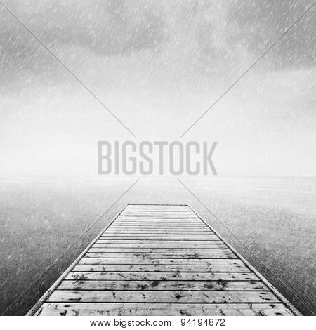 Wooden jetty, pier on deep cold sea, ocean. Raining sky, scandinavian mood, copy-space. Black and white.