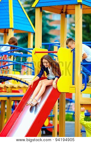 Group Of Happy Kids Sliding In Colorful Playground