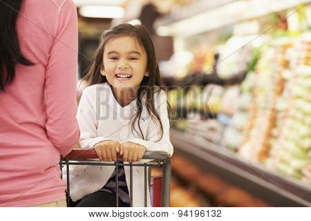 Close Up Of Mother Pushing Daughter In Supermarket Trolley