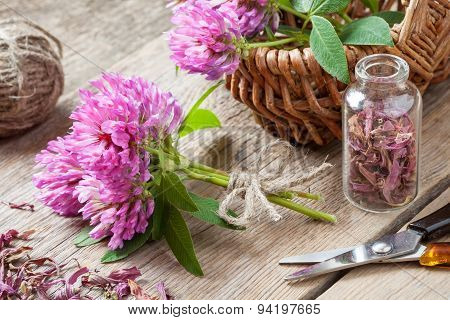Bunch Of Clover, Bottle With Dried Herb And Basket With Flowers On Wooden Table.