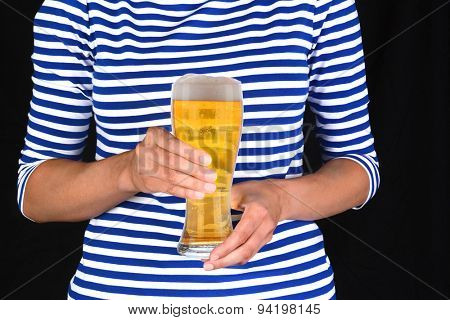 Closeup of a woman holding a cold glass of beer in front of her torso. The unrecognizable female is wearing a blue striped blouse.