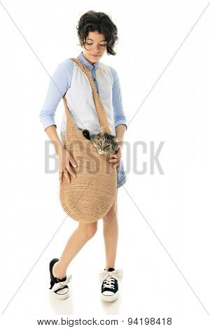 Full-length image of a pretty young teen carrying her cat in a large, woven shoulder bag.  Focus is on the girl.  On a white background.