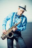 stock photo of saxophones  - Young expressive musician playing the saxophone - JPG