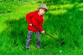 pic of 7-year-old  - Cute 7 years old boy playing golf outdoor - JPG