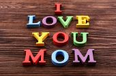stock photo of i love you mom  - Inscription I LOVE YOU MOM made of colorful letters on wooden background - JPG