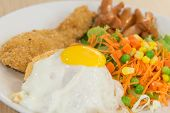 stock photo of fried chicken  - Thai American fusion style fried rice with fried egg and fried chicken served with salad closeup focused on yolk - JPG