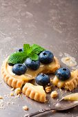 picture of curd  - Shortbread home made broken tartlet filled with lime curd and blueberries on old vintage metal background - JPG