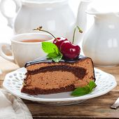 picture of high calorie foods  - Slice of delicious chocolate mousse cake with cherries and mint over white - JPG