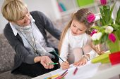 stock photo of homework  - Grandmother helping granddaughter with homework at home - JPG