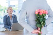 foto of office romance  - Businessman hiding flowers behind back for colleague in an office - JPG