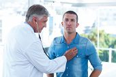 foto of auscultation  - Doctor auscultating his patients chest in medical office - JPG