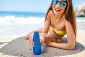 stock photo of suntanning  - Woman showing suntan cream bottle on the beach - JPG
