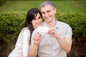 pic of two women taking cell phone  - Young attractive happy smiling lovers couple in love sitting on park bench on date hugging holding cellphone looking at screen together taking self portrait picture with mobile phone - JPG