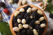 picture of mulberry  - White and black mulberries in a wooden bowl on the table close - JPG