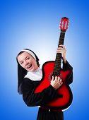 stock photo of nun  - Nun playing guitar against the gradient  - JPG