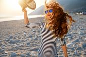 image of hands-free  - Young and happy woman in stripped dress jumping with a hat in the hand on the beach on sunset against the sun - JPG