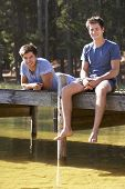 stock photo of jetties  - Two Men Sitting On Wooden Jetty Looking Out Over Lake - JPG
